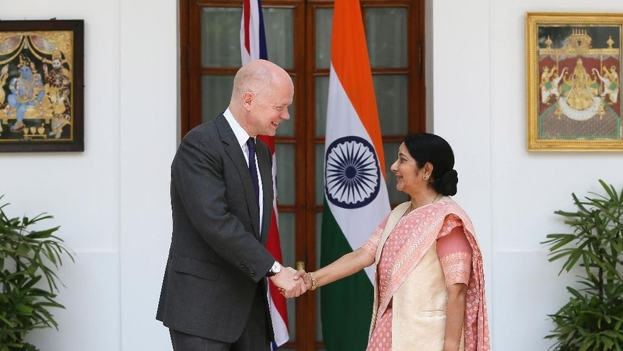 Indian Foreign Minister Sushma Swaraj, right, shakes hand with British Foreign Secretary William Hague, in New Delhi, India ,Tuesday, July 8, 2014. (AP Photo /Manish Swarup)