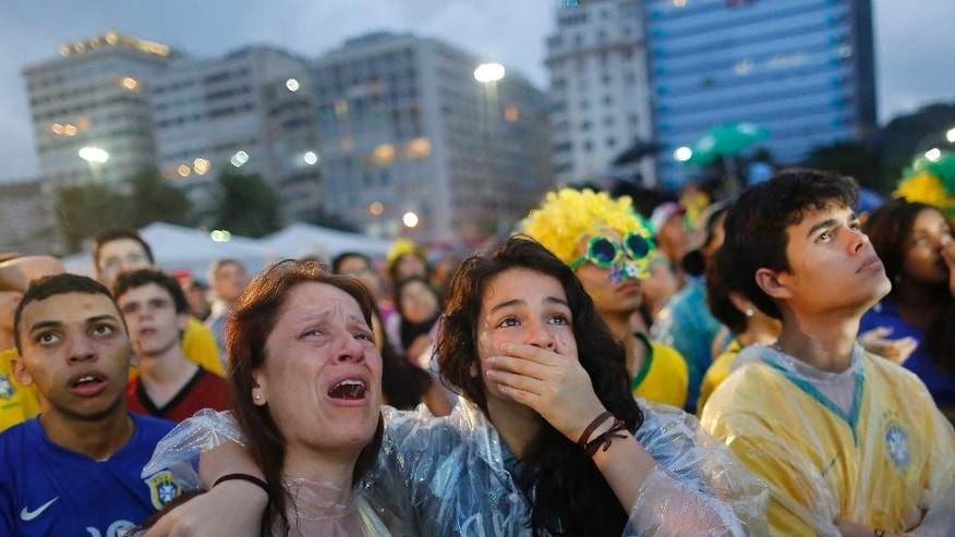 Brazil soccer fans cry as they watch their team lose 7-1 to Germany at a World Cup semifinal match on a live telecast inside the FIFA Fan Fest area on Copacabana beach in Rio de Janeiro, Brazil, Tuesday, July 8, 2014. (AP Photo/Leo Correa)
