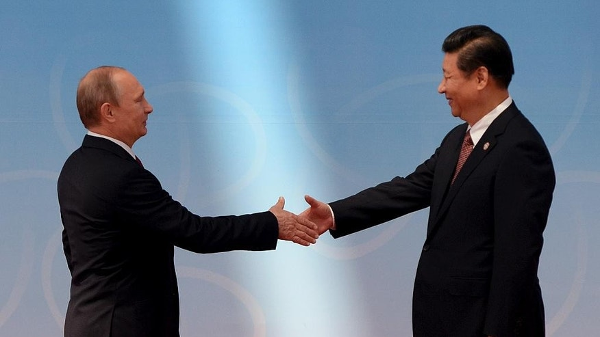 FILE - In this May 21, 2014 file photo, Russian President Vladimir Putin, left, is greeted by Chinese President Xi Jinping before the opening ceremony at the fourth Conference on Interaction and Confidence Building Measures in Asia (CICA) summit in Shanghai, China. Moscow is cozying up to its old rival China. China is holding hands with Seoul. Tokyo is striking deals with Pyongyang. In the ever-shifting game of Asian alliances, where just about everybody has a dispute over something or can actually remember a shooting war with their neighbors, past grudges run deep. But expedience and pragmatism often run deeper. (AP Photo/Mark Ralston, Pool, File)