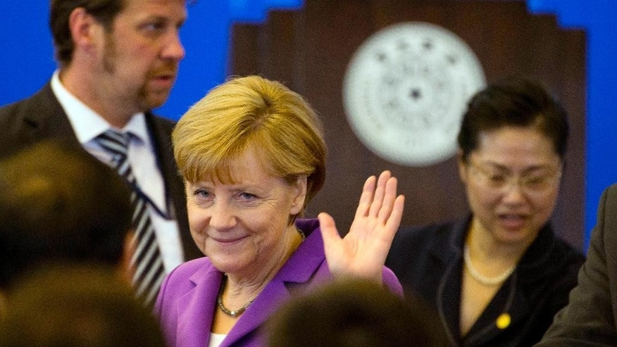 German Chancellor Angela Merkel waves upon arrival to deliver a speech at Tsinghua University in Beijing, China, Tuesday, July 8, 2014. (AP Photo/Ng Han Guan)
