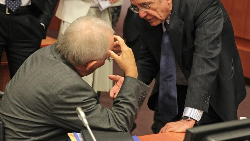 Italian Finance Minister and President of the rotating EU Council Pier Carlo Padoan, right, talks with German Finance Minister Wolfgang Schaeuble, during the eurogroup ministerial meeting, at the European Council building in Brussels, Monday, July 7, 2014. (AP Photo/Yves Logghe)