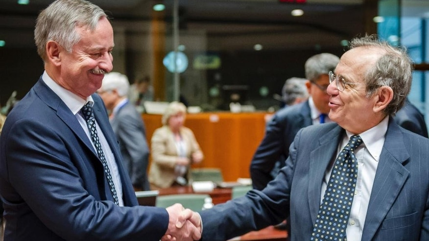 Italian Finance Minister Pier Carlo Padoan, right, greets Vice President of the European Commission Siim Kallas during a EU finance ministers meeting at the European Council building in Brussels, Tuesday, July 8, 2014. (AP Photo/Geert Vanden Wijngaert)