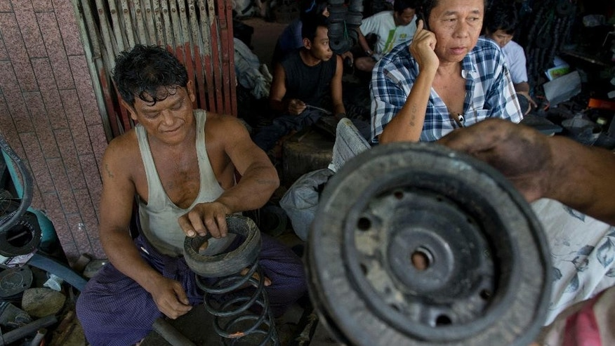 In this June 23, 2014 photo, a worker matches a rubber bush made out of a warn out tire with a shock absorber of a vehicle at suburban tire reutilize shop in Yangon, Myanmar. During Myanmar's half-century of dictatorship and self-imposed isolation, the country went from being one of the region's richest to the poorest. Businesses were nationalized and everything from toothpaste to rice rationed. Only a few cars, all belonging to the ruling elite, bounced along the pot-holed roads and getting spare parts was next to impossible. (AP Photo/Gemunu Amarasinghe)