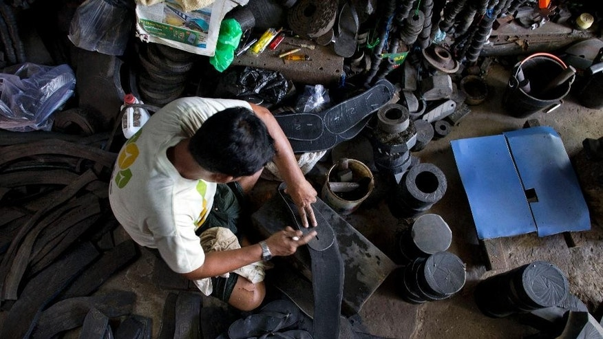 In this June 23, 2014 photo, a worker marks a shape of footwear on a slice of a warn out tire, at a suburban tire reutilize shop in Yangon, Myanmar. Rubber, thong slippers that are by far the most popular footwear in the rural areas, are among the biggest sellers for tire recyclers. They are especially popular among farmers. (AP Photo/Gemunu Amarasinghe)