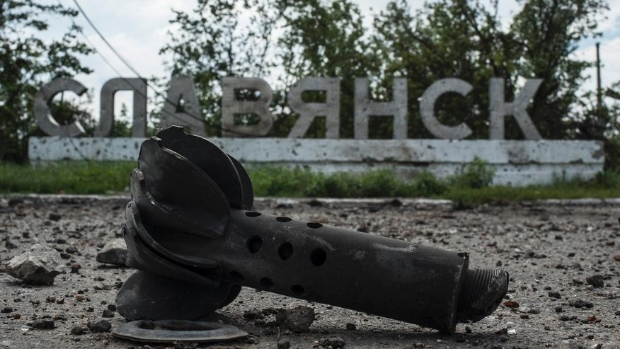 A part of the mortar shell is seen in front of a sign that reads 'Slovyansk', after heavy fighting between pro-Russian fighters and Ukrainian government troops just outside Slovyansk, eastern Ukraine, Wednesday, July 9, 2014. The rebels fled Slovyansk, a city of 100,000 that had been their stronghold, over the weekend as Ukrainian troops mounted an offensive. They left behind a city heavily damaged by fighting and riven by vehemently differing views. (AP Photo/Evgeniy Maloletka)