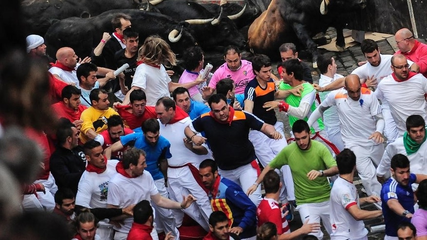Revelers run ahead of ''Jandilla'' fighting bulls on Estafeta corner on the way to the bull ring, during the running of the bulls, at the San Fermin festival, in Pamplona, Spain, Friday, July 11, 2014. Revelers from around the world arrive to Pamplona every year to take part in some of the eight days of the running of the bulls. (AP Photo/Alvaro Barrientos)