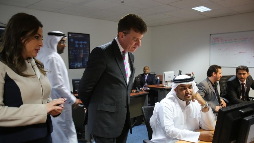 In this June 17, 2014, photo,  Dubai Airports CEO Paul Griffiths, center, a 56-year-old Briton, visits the Joint Control Room which is essentially the nerve center of operations for the airport in Dubai, United Arab Emirates. Now that he's had a taste of running the world's busiest air hub for international passengers, Griffiths is determined to hang on to the honor while setting his sights on an even bigger prize: beating Atlanta for the title of busiest airport on the planet. (AP Photo/Kamran Jebreili)