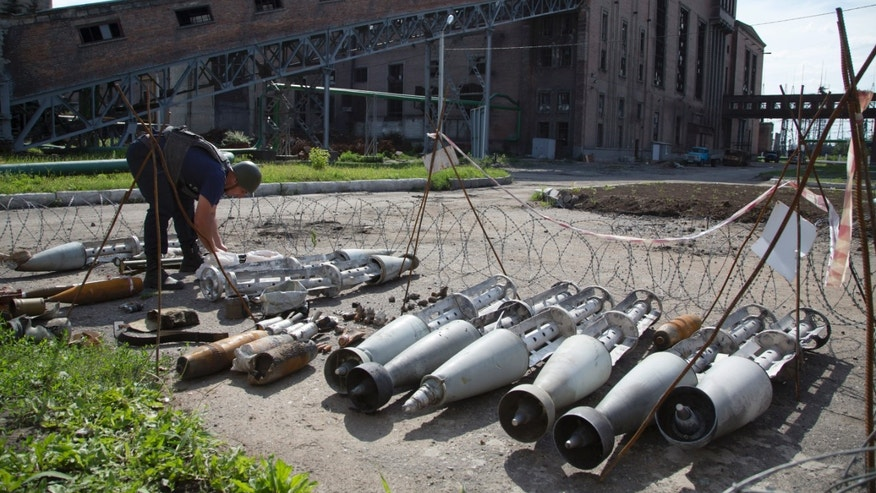 "July 10, 2014 - A member of the rescue service works near fragments of a multiple missile ""Smerch"" found after an attack by Ukrainian government forces at a power station outside the city of Slovyansk, Donetsk Region, eastern Ukraine. In the past two weeks, Ukrainian government troops have halved the amount of territory held by the rebels."