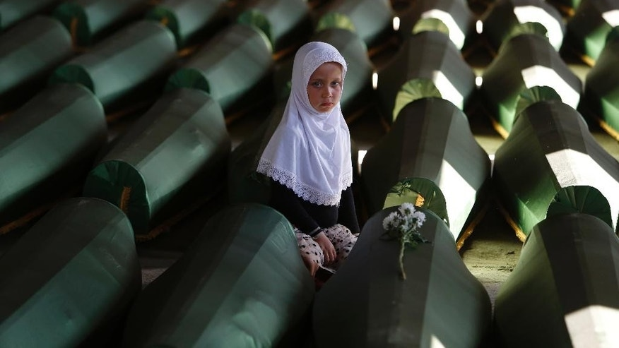 Ema Hasanovic, 5, a young Bosnian Muslim girl, pays her respects near to the coffin of her uncle, in the Memorial center in Potocari, 200 kms northeast of Sarajevo, on Wednesday, July 9, 2014. Hundreds of people turned out in Sarajevo's main street to pay their respects to 175 victims of the Srebrenica massacre — Europe's worst since World War II — as a truck carried their coffins to a final resting place. The remains of the men and boys, found in mass graves and identified through DNA analysis, will be buried in Srebrenica on Friday, the 19th anniversary of the massacre, next to 6,066 previously found victims. (AP Photo/Amel Emric)