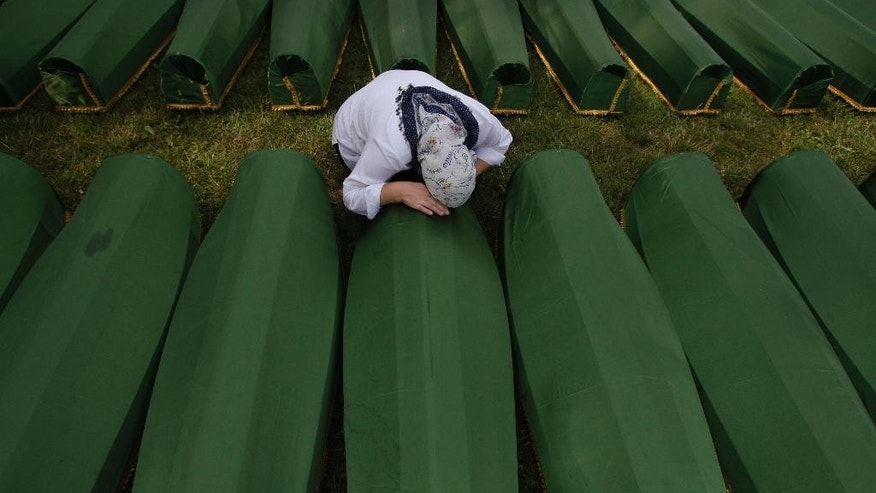FILE - This is a Thursday, July 11, 2013 file photo of a Bosnian woman as she cries near the coffin of her relative during a funeral ceremony at the memorial center in Potocari, near Srebrenica, 160 kms east of Sarajevo, Bosnia, Thursday, July 11, 2013. People from around Bosnia and abroad have begun arriving in Srebrenica Thursday to commemorate 18th anniversary of the 1995 massacre and rebury recently identified victims exhumed from mass graves. Hundreds of people lined Sarajevo's main street on Wednesday July 9, 2014 to pay their respects as coffins carrying the remains of 175 victims of Europe's worst massacre since World War II passed by.  (AP Photo/Amel Emric, File)