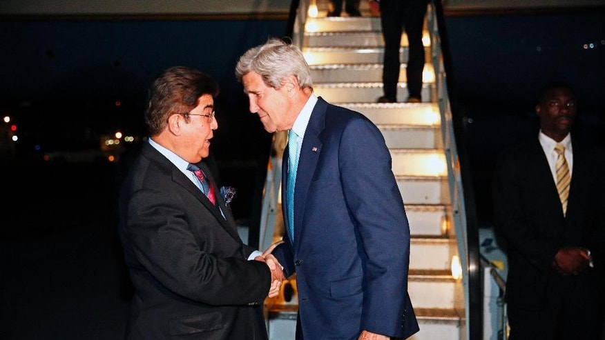 U.S. Secretary of State John Kerry, centre, talks with Afghanistan's Ministry of Foreign Affairs chief of protocol Ambassador Hamid Siddiq, as Kerry arrives at Kabul International airport in Kabul, Friday July 11, 2014. Kerry is expected to meet with Afghanistan's President Kharzai as well as both candidates in Afghanistan's recent presidential election.  (AP Photo/Jim Bourg, Pool)