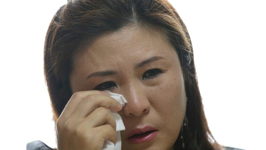 In this April 11, 2014 photo,  Won Jeong-hwa wipes a tear during an interview at her apartment in Gunpo, south of Seoul, South Korea. Once their espionage cases are resolved, some former North Korean spies find that life in the South can be pretty good. They write books, land TV gigs, work for think tanks and in general benefit from their new home's fascination with their old homeland. Won is not one of those spies. A year after finishing a five-year espionage sentence for using sex to obtain military secrets and plotting to assassinate intelligence officers, Won is a 40-year-old single mother eking out a living on an $800 monthly government subsidy. Her espionage work is not taken seriously enough in South Korea for her to cash in on her past, yet she's too notorious to find an ordinary job. (AP Photo/Lee Jin-man)