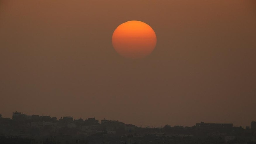 The sun sets over the Gaza Strip, as seen from the Israel-Gaza border, on Friday, July 11, 2014. Gaza rocket fire by Palestinian militants struck a gas station and set it ablaze Friday in southern Israel, seriously wounding one person as rocket fire also came from Lebanon for the first time in the four-day-long offensive. Rocket fire by Palestinian militants continued from Gaza toward various locations in southern Israel. (AP Photo/Lefteris Pitarakis)