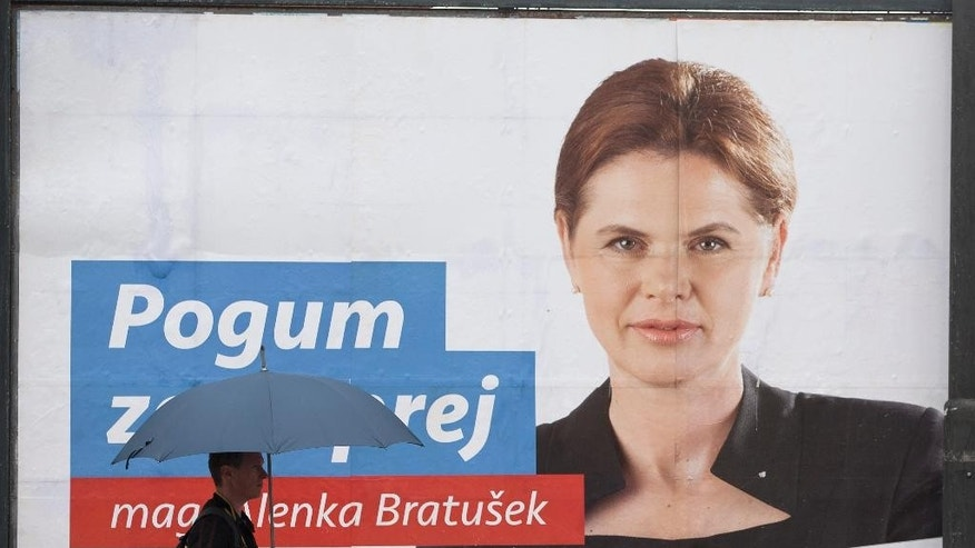 "In this photo taken Thursday, July 10, 2014, a pedestrian walks past an election poster of outgoing prime minister Alenka Bratusek, in Ljubljana, Slovenia. Slovenia is holding a snap parliamentary vote on Sunday to choose a third government in three years. The text on poster reads: ""courage"" and ""alliance"". (AP Photo/Darko Bandic)"