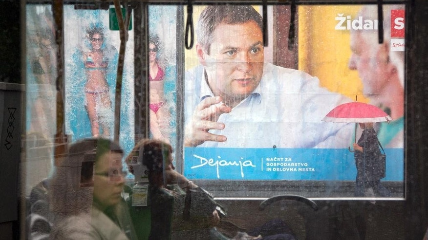 In this photo taken Thursday, July 10, 2014, residents ride on a public bus past an election poster for the center-left Social Democrats, in Ljubljana, Slovenia. Slovenia is holding a snap parliamentary vote on Sunday to choose a third government in three years. (AP Photo/Darko Bandic)