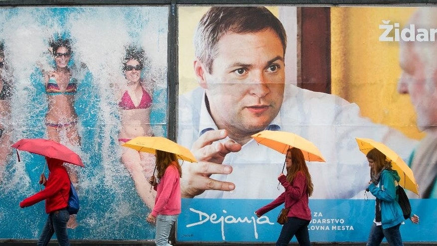 In this photo taken Thursday, July 10, 2014, pedestrians walk in front of an electoral poster and a holiday advertisement in Ljubljana, Slovenia. Slovenia is holding a snap parliamentary vote on Sunday to choose a third government in three years. (AP Photo/Darko Bandic)