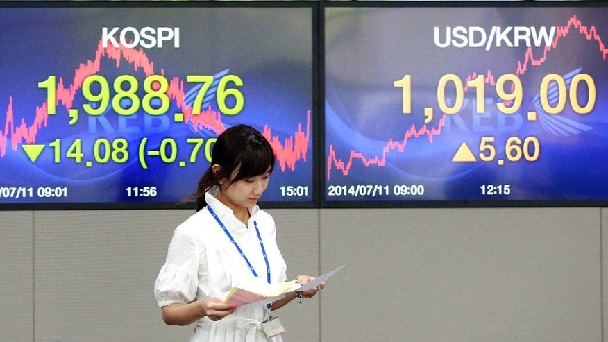 A currency trader passes by screens showing the Korea Composite Stock Price Index, left, and the exchange rate between the U.S. dollar and the South Korean won at the foreign exchange dealing room of the Korea Exchange Bank headquarters in Seoul, South Korea, Friday, July 11, 2014. Asian stock markets were muted Friday, following the lead of Wall Street traders spooked by worries about the soundness of a bank in Portugal that raised the specter of more financial turmoil in Europe. South Korea's benchmark Kospi dropped 0.70 percent at 1,988.74.( AP Photo/Ahn Young-joon).