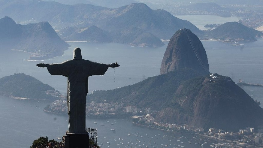 FILE - In this June 27, 2014 file photo, Christ the Redeemer statue is silhouetted next to Sugar Loaf Mountain, in Rio de Janeiro, Brazil. Rio's Archbishop Orani Tempesta presided over a ceremony Friday, July 11, 2014, marking the end to repairs made to the city's famed statue. The $856,000 repair project began six months ago after two fingers and part of the statue's head were chipped during lightning storms. (AP Photo/Leo Correa, File)