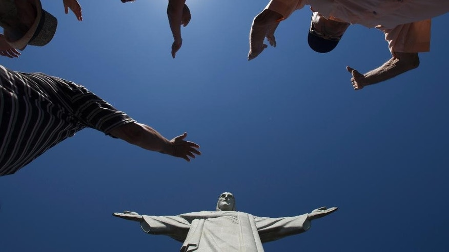 FILE - In this Tuesday, Jan. 21, 2014 photo, visitors raise their arms to pray below the Christ Redeemer statue in Rio de Janeiro, Brazil. Rio's Archbishop Orani Tempesta presided over a ceremony Friday, July 11, 2014, marking the end to repairs made to the city's famed statue. The $856,000 repair project began six months ago after two fingers and part of the statue's head were chipped during lightning storms. (AP Photo/Felipe Dana, File)