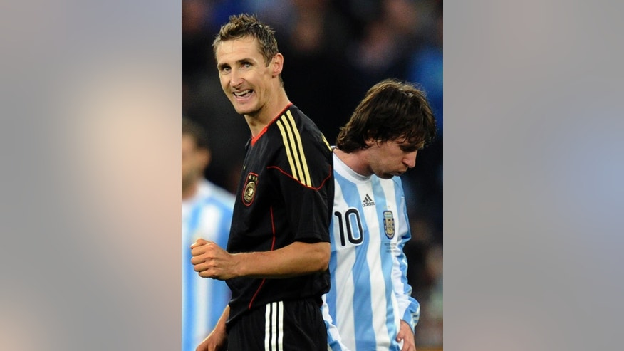 FILE - The July 3, 2010 file photo shows Germany's Miroslav Klose, left, walking past Argentina's Lionel Messi as he celebrates after scoring his team's fourth goal during the World Cup quarterfinal soccer match between Argentina and Germany at the Green Point stadium in Cape Town, South Africa. Germany won 4-0. On Sunday, July 13, 2014, Germany and Argentina will face each other again in the final of the 2014 soccer World Cup. (AP Photo/Martin Meissner, file)