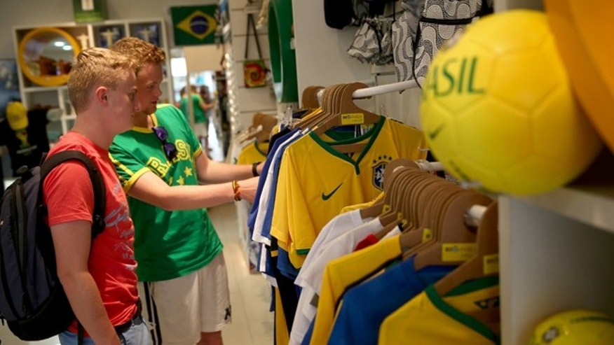 RIO DE JANEIRO, BRAZIL - JUNE 09: George Mackenzie Smith and Tom Simmonds ,both from Scotland, shop for World Cup souvenirs in a Rio in Box store on June 9, 2014 in Rio de Janeiro, Brazil.   Brazil continues to prepare to host the World Cup which starts on June 12th and runs through July 13th.  (Photo by Joe Raedle/Getty Images)