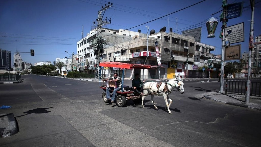 A Palestinian man drives a donkey cart on an empty main road in Gaza City on Friday, July 11, 2014. It's the holy month of Ramadan, and throughout the Muslim world people are socializing with friends and family, buying presents for loved ones and breaking a day long fast amid colorful night time street scenes that inject even more vigor into already busy urban centers. But not in Gaza City, one of the world's most densely populated cities. A ceaseless Israeli bombing campaign, with airstrikes every five minutes, has turned the frenetic hub of the Gaza Strip into a virtual ghost town, emptying streets, closing shops and keeping hundreds of thousands of people close to home where they feel safest from the bombs. (AP Photo/Khalil Hamra)