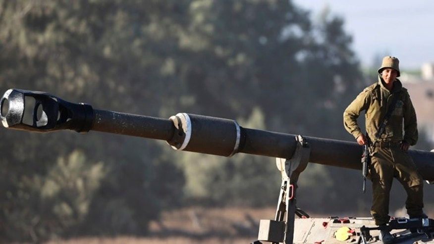 July 11, 2014: An Israeli soldier leans on the barrel of the gun of a mobile artillery unit at a position on the Israel-Gaza border. (AP)