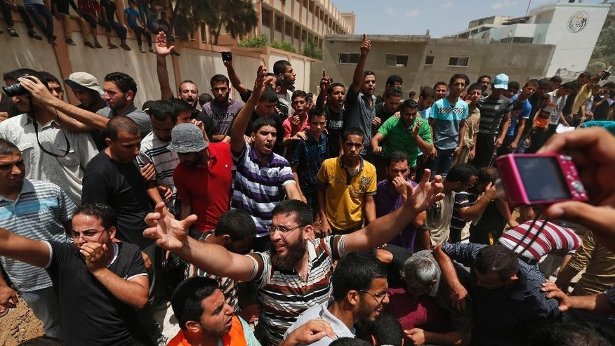 CAPTION CORRECTION, CORRECTS THE HOME WAS THAT OF POLICE CHIEF'S COUSIN - Palestinian mourners gather around the grave of a member of the al-Batsh family who were killed in Saturday's Israeli airstrike, during a funeral procession in Gaza City on Sunday, July 13, 2014. The strike hit the home of a cousin of Gaza police chief Taysir al-Batsh and damaged a nearby mosque as evening prayers ended Saturday, killing at least 18 people, wounding 50 and leaving some people believed to be trapped under the rubble, said Palestinian Health Ministry official Ashraf al-Kidra. (AP Photo/Lefteris Pitarakis)