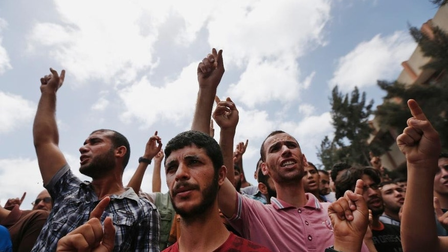 CAPTION CORRECTION, CORRECTS THE HOME WAS THAT OF POLICE CHIEF'S COUSIN - Palestinian mourners chant slogans during a funeral procession of a member of the al-Batsh family who were killed in Saturday's Israeli airstrike, during a funeral procession in Gaza City on Sunday, July 13, 2014. The strike hit the home of a cousin of Gaza police chief Taysir al-Batsh and damaged a nearby mosque as evening prayers ended Saturday, killing at least 18 people, wounding 50 and leaving some people believed to be trapped under the rubble, said Palestinian Health Ministry official Ashraf al-Kidra. (AP Photo/Lefteris Pitarakis)