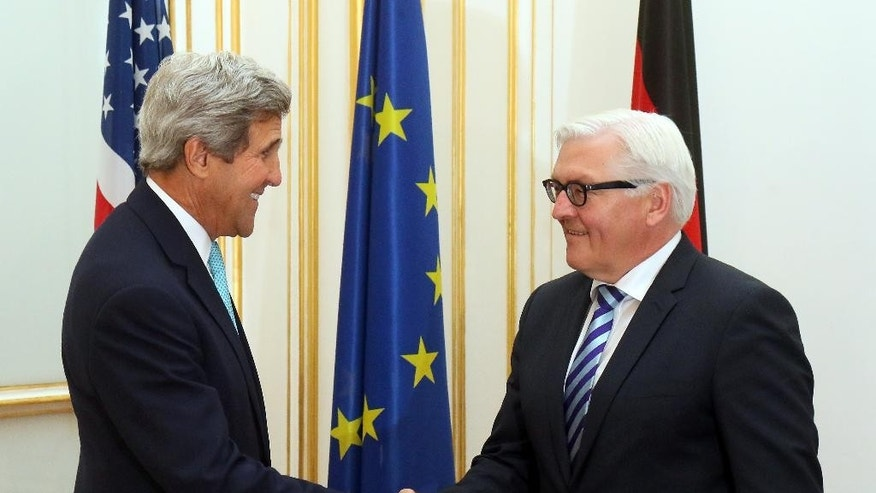 U.S. Secretary of State John Kerry, left, shakes hands with German Foreign Minister Frank-Walter Steinmeier, right, at a hotel where closed-door nuclear talks take place in Vienna, Austria, Sunday, July 13, 2014. Kerry meets separately with Steinmeier to discuss a spiraling espionage dispute between the close NATO partners. (AP Photo/Ronald Zak)