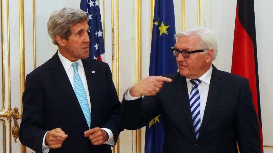 U.S. Secretary of State John Kerry, left, meets with German Foreign Minister Frank-Walter Steinmeier, right, at a hotel where closed-door nuclear talks take place in Vienna, Austria, Sunday, July 13, 2014. Kerry meets separately with Steinmeier to discuss a spiraling espionage dispute between the close NATO partners. (AP Photo/Ronald Zak)