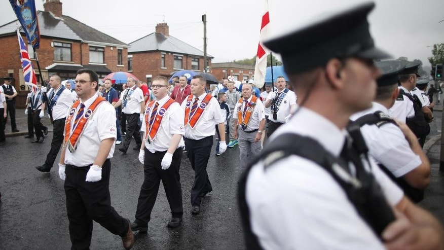 Orange Order members parade past the Ardoyne area of North Belfast, Northern Ireland, Saturday, July 12, 2014. Thousands of Protestant bands and Orange Order members paraded across many parts of Northern Ireland Saturday for the Twelfth of July celebrations an annual Protestant commemoration of the 1690 Battle of the Boyne. (AP Photo/Peter Morrison)