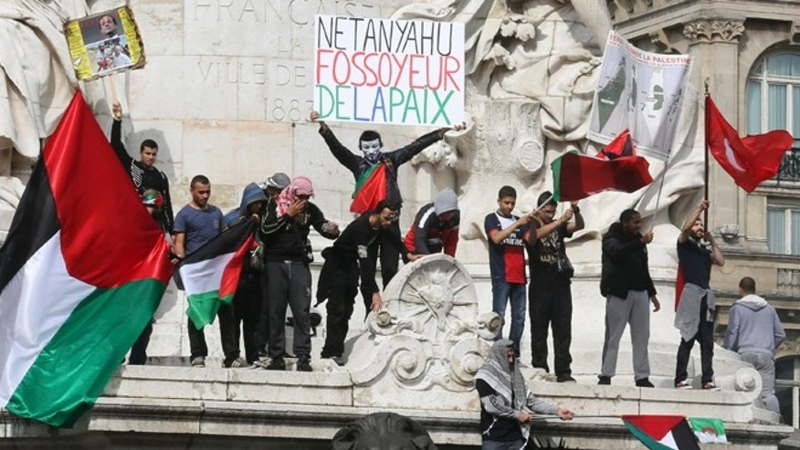 "July 13, 2014: Pro-Palestinian demonstrators wave Palestinian flags and chant anti Israeli slogans on the statue of Republic in Paris, to protest against the Israeli army's bombings in the Gaza strip. Banner reads: ""Netanyahu gravedigger of peace."" About 10,000 pro-Palestinian protesters marched through eastern Paris on Sunday demanding an end to Israeli strikes on Gaza, and accusing Western leaders of not doing enough to stop them."
