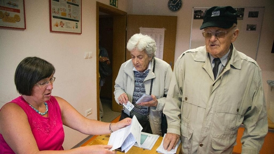 Voters register at a polling station in Ljubljana, Slovenia, Sunday, July 13, 2014. Slovenes are voting in the second early election in three years amid political instability that threatened the small euro zone nation's bid to pull out of an economic downturn. (AP Photo/Darko Bandic)