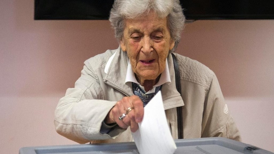 A voter casts her ballot at a polling station in Ljubljana, Slovenia, Sunday, July 13, 2014. Slovenes are voting in the second early election in three years amid political instability that threatened the small euro zone nation's bid to pull out of an economic downturn. (AP Photo/Darko Bandic)