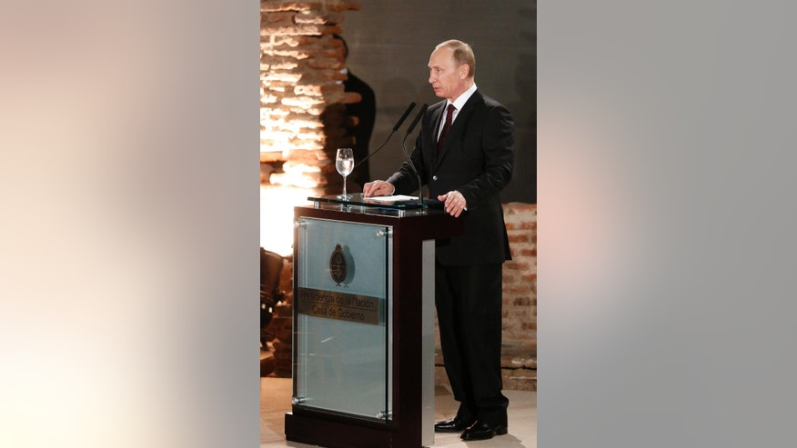 Russian President Vladimir Putin, talks during an official dinner at Government Palace, in Buenos Aires, Argentina, Saturday, July 12, 2014. Putin is in a one-day official visit to Argentina and will next stop in Brazil for a presidential summit of the BRICS group of nations in Fortaleza. He was also to attend the final World Cup match in a ceremonial handover of host duties for soccer's marquee tournament, which takes place in Russia in 2018. (AP Photo/Jorge Saenz)