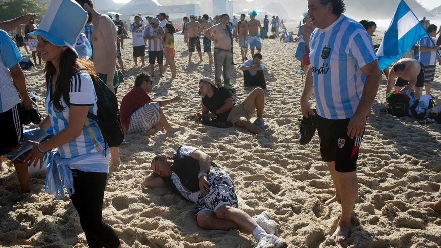 Argentina soccer fans gather after spending the night on Copacabana Beach in Rio de Janeiro, Brazil, Sunday, July 13, 2014. Argentina will face Germany in the World Cup final today Sunday July 13. (AP Photo/Rodrigo Abd)