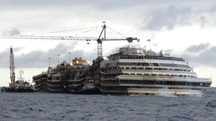 FILE -- In this file photo taken on Jan. 23, 2014, the Costa Concordia cruise liner lies in the waters of the Giglio Island, Italy. Italian authorities say work to float the shipwrecked Costa Concordia so it can be towed away for scrapping can start Monday, weather-permitting. (AP Photo/Luigi Navarra)