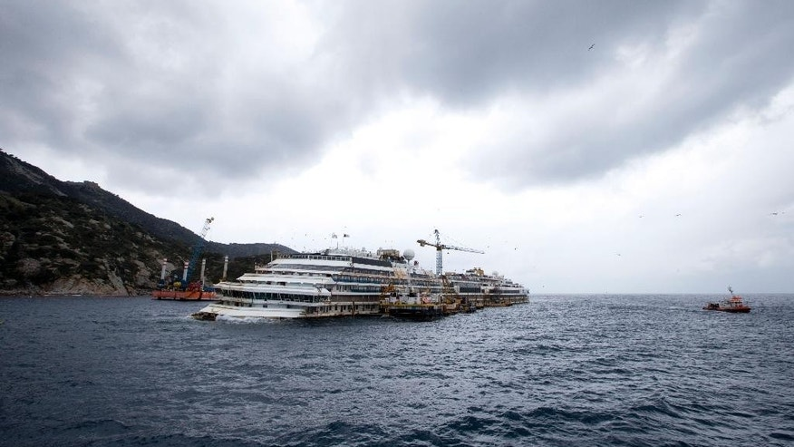 FILE - In this Feb. 26, 2014 file photo the wreck of the Costa Concordia cruise ship is seen from a ferry boat approaching Tuscan Island of Giglio, Italy. Italian authorities say work to float the shipwrecked Costa Concordia so it can be towed away for scrapping can start Monday, weather-permitting.  (AP Photo/Andrew Medichini, file)