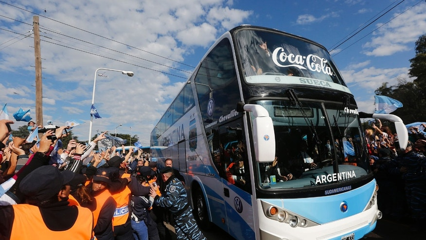 Argentina's soccer team arrives in a bus as fans gather to welcome them home in Buenos Aires, Argentina, Monday, July 14, 2014. Argentina was defeated 1-0 by Germany at the the Brazil World Cup final match on Sunday. (AP Photo/Daniel Jayo)