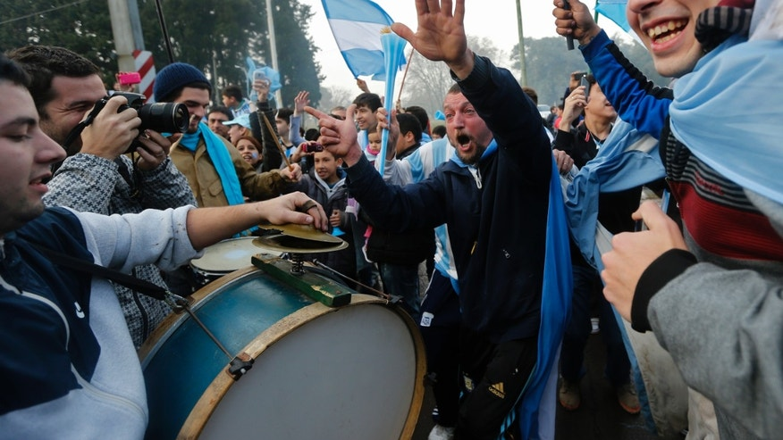 Argentina soccer fans cheer and play drums as they wait for the arrival of their team to Buenos Aires, Argentina, Monday, July 14, 2014. Fans came out to welcome home Argentina's team after it was defeated 1-0 by Germany at the Brazil World Cup final match on Sunday. (AP Photo/Daniel Jayo)