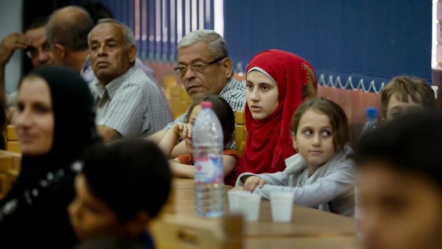 Romanians and Palestinians of mixed families attend a briefing after arriving on a military plane from Gaza, at the Romanian Air Force Base 90, outside Bucharest, Romania, Monday, July 14, 2014. A group of 84 people from mixed Romanian-Palestinian families fled the conflict area and were flown out of the Gaza strip at their request by the Romanian authorities. (AP Photo/Vadim Ghirda)