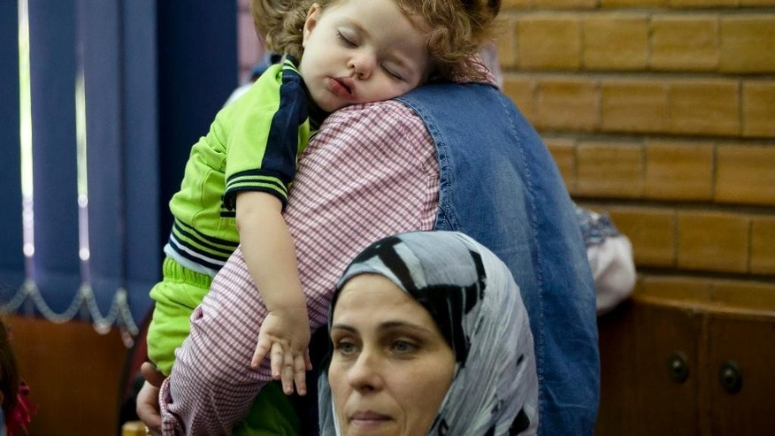A child sleeps in a woman's arms after arriving on a military plane from Gaza, at the Romanian Air Force Base 90, outside Bucharest, Romania, Monday, July 14, 2014. A group of 84 people from mixed Romanian-Palestinian families fled the conflict area and were flown out of the Gaza strip at their request by the Romanian authorities. (AP Photo/Vadim Ghirda)