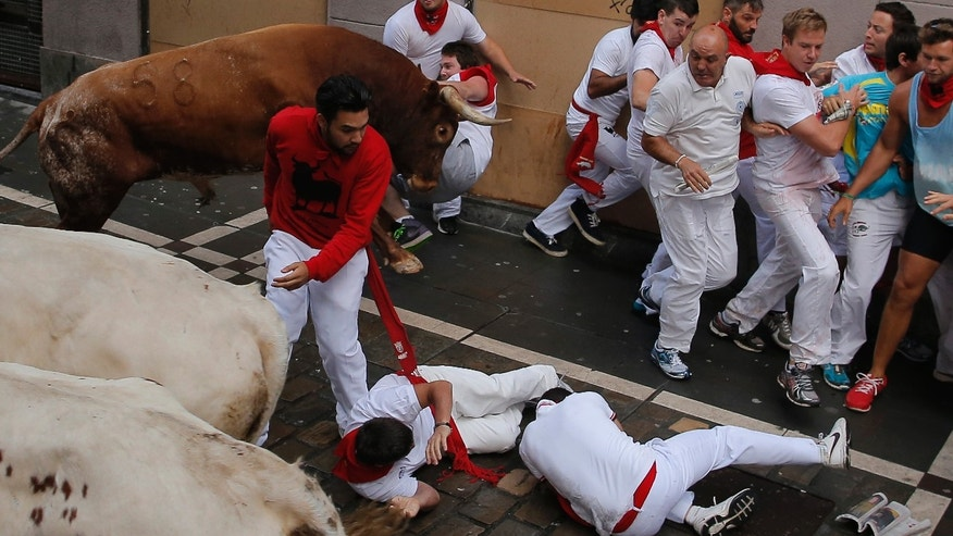 July 14, 2014 - A reveler is tossed by a Miura fighting bull as others fall during the running of the bulls at the San Fermin festival, in Pamplona, Spain.