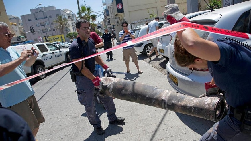 FILE - In this file photo taken July 11, 2014, Israeli explosives experts carry the remnants of a long-range rocket fired by Palestinians militants from Gaza after being shot down by Israel's Iron Dome air defense system and hit a synagogue in Tel Aviv, Israel. Israel says its punishing air assault on Hamas militants, their property and their weaponry has delivered a devastating blow to the Islamic militant group. Yet rocket fire at Israel has continued almost unabated. (AP Photo/Oded Balilty, File)