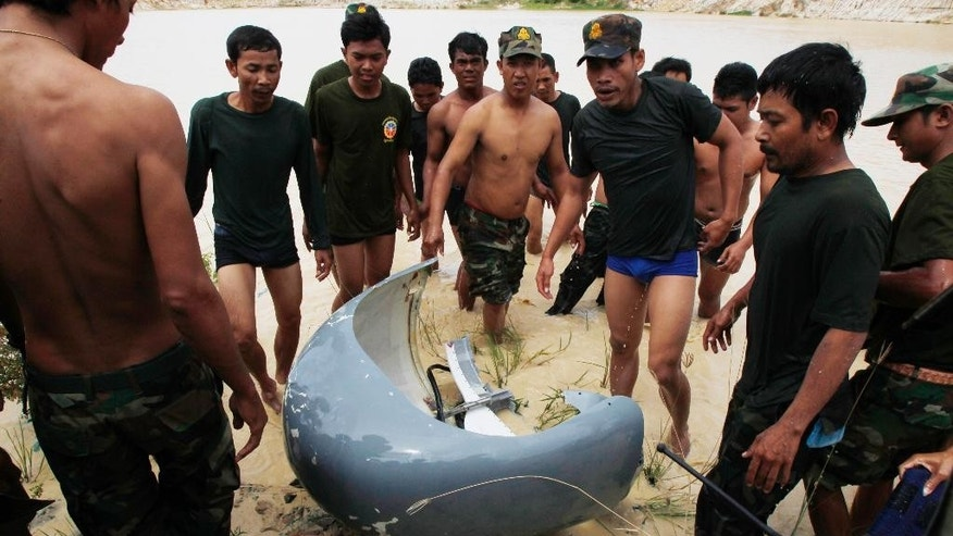 Rescue workers gather around a part of a crashed helicopter retrieved from a pond, a site of an helicopter crash in Prey Sar village at the outskirt of Phnom Penh, Cambodia, Monday, July 14, 2014. A Cambodian military helicopter crashed during a training mission south of the capital on Monday, killing five people on board, police said.(AP Photo/Heng Sinith)