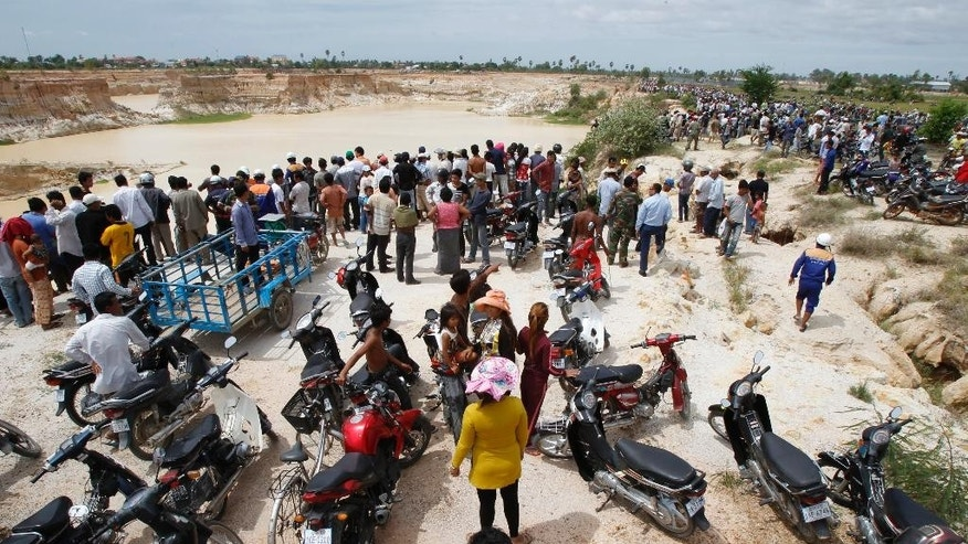 Villagers watch a site of an helicopter crash in Prey Sar village at the outskirt of Phnom Penh, Cambodia, Monday, July 14, 2014. A Cambodian military helicopter crashed during a training mission south of the capital on Monday, killing five people on board, police said. (AP Photo/Heng Sinith)