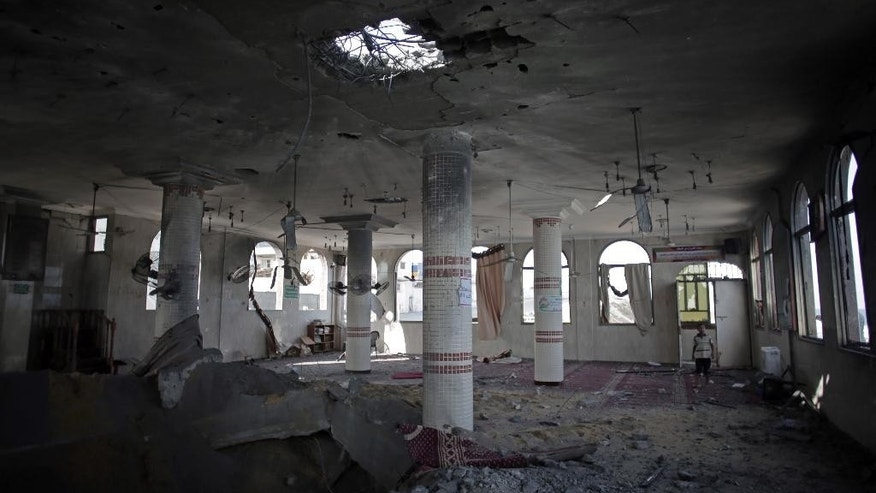 July 14, 2014 - A Palestinian looks at a mosque following an overnight Israeli missile strike in Gaza City.