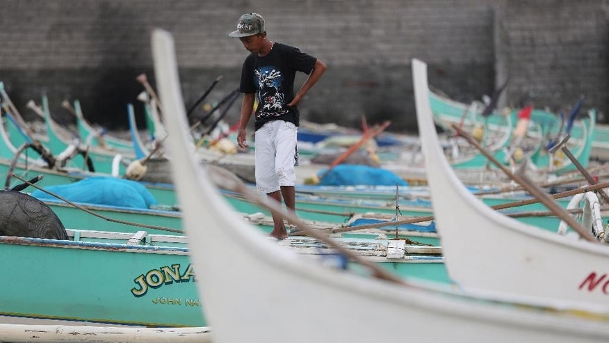 "A Filipino walks small fishing boats docked beside a coastal village of Navotas, north of Manila, Philippines as they prepare for a coming storm on Monday, July 14, 2014. The Philippines is bracing for possible floods and landslides as Tropical Storm Rammasun, locally called ""Glenda"", intensified while moving closer to the eastern seaboard. (AP Photo/Aaron Favila)"