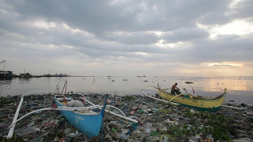 "A Filipino fisherman covers parts of his boat that is docked on top of piles of garbage as he prepares for a coming storm along a coastal village in Navotas, north of Manila, Philippines on Monday, July 14, 2014. The Philippines is bracing for possible floods and landslides as Tropical Storm Rammasun, locally called ""Glenda"", intensified while moving closer to the eastern seaboard. (AP Photo/Aaron Favila)"